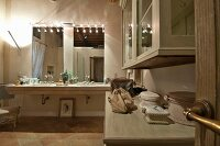 Spacious bathroom; illuminated washstand with twin sinks and two mirrors