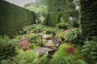 Idyllic green garden wit tall hedge, stone-flagged path, stream and wooden bridge