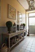 Lanterns and small bushes decorating console table in rustic hallway