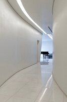 Glossy white marble floor and strip light in ceiling in curved hallway leading to grand piano in room at far end