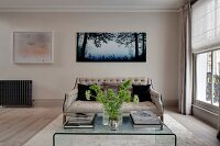 Elegant button-tufted sofa, plexiglas coffee table and pictures on wall in living room