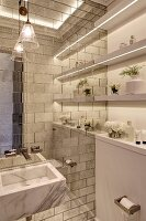 Elegant bathroom with marble sink on tiled wall and strip lights integrated into shelves