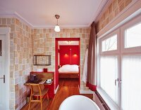 Small table in ensuite bathroom next to doorway leading into bedroom with bright red wall
