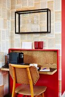 Chair at small red bureau with fold-down desk against wall covered in designer wallpaper