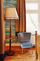Easy chair with slate grey velvet cover next to fifties-style standard lamp with wooden base and integrated shelf in bedroom