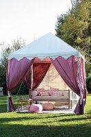 Shady seating area in garden in style of Bedouin tent with draped purple curtains