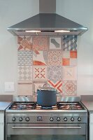 Splashback made from painted tiles with various patterns behind gas cooker