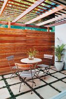 Bistro table and chairs on flagged terrace with plants growing in wide paving joints, wooden wall and pergola roof