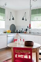Round wooden table and red chairs in kitchen with white base units