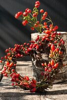 Small wreath of rose hips on wooden table