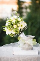 Festive bouquet of white flowers in concrete pot decorated with ribbon