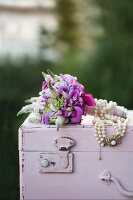 Festive posy decorated with bead necklace on wooden trunk painted pastel pink