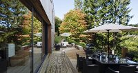 Table, chairs and parasol outside modern wooden house