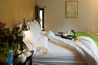 Tray on double bed with white bedlinen and retro table lamp on bedside table in modern bedroom