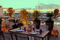 Set table on terrace with lit candle lanterns in front of tall planters against balustrade; yachting marina in background at sunset