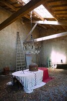 Table with tablecloths below chandelier suspended from wooden ceiling with skylight in old barn