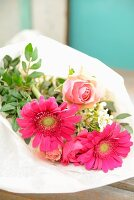 Bouquet of roses, gerbera daisies and waxflowers wrapped in tissue paper
