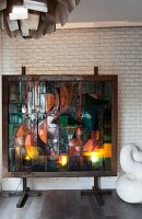 Glass backlit artwork mounted in front of white brick wall