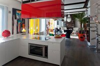 White L-shaped kitchen counter with red-painted extractor hood and lounge area in background