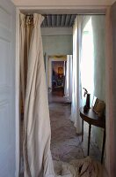 View of delicate console table on vintage stone floor through open doorway with floor-length curtain