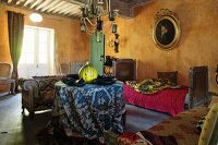 Round table with patterned tablecloth, sofa and antique daybed against wall painted ochre in rustic interior