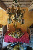 Vintage daybed against wall painted ochre; pendant chandelier decorated with lanterns in foreground