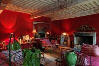 Atmospheric living area with lit table lamps, red walls, vintage daybeds and open fireplace