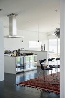 Ethnic rug in dining area in front of island counter in open-plan designer kitchen
