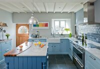 Country-house kitchen with pale blue fronts and central counter with marble and walnut worksurfaces