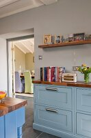 Country-house kitchen with pale blue fronts and walnut worksurface