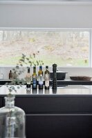 Vinegar and oil bottles on kitchen counter in front of window with a view
