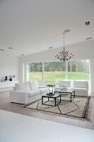 Elegant white two-seater sofa and matching armchair around two coffee tables on rug below chandelier; view of garden through large window