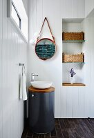 Modern cylindrical washstand with countertop basin in corner of white wood-clad bathroom