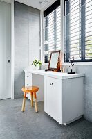 Simple orange dip-dye stool at white dressing table below windows with louvre blinds
