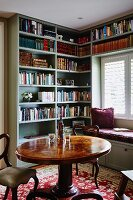 Round table and antique-style chairs in front of fitted bookcases and custom window seat