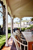 Wicker chairs at wooden table on veranda with white-painted wooden pillars