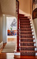 Striped runner on white-painted wooden staircase in rustic hallway; open door with view of dining area in background