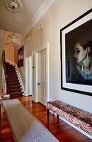Upholstered bench below portrait of woman on wall and staircase in background in traditional elegant hallway