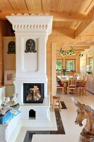 White ornate stove in living room of elegant wooden house with carved decorations