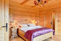 Double bed with curved headboard and purple silk cover in solid wooden house