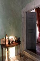Delicate antique console table next to open double doors in rustic, Mediterranean interior
