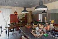 Crockery on island counter with gas hob below vintage-style pendant lamps and dining set in background in modern rustic interior