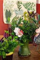Green vase of flowers on table in front of vintage botanical illustration