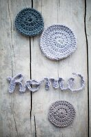 Crocheted cord arranged to spell 'Home' and round pastel castors on vintage wooden surface