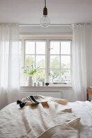 Off-white bedspread on bed below lattice window in rustic bedroom