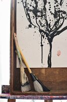 Various paintbrushes in front of black and white painting in wooden frame