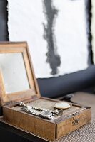 Watches displayed in open, vintage, wooden box with mirror inside lid