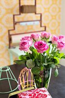 Glass vase of pink roses and pastel lampshade frames
