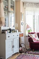 Pale grey dresser and vintage-style standard lamp next to claret-red armchair in window bay