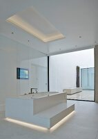 Free-standing bathtub with step in white, minimalist designer bathroom with indirect lighting in floor and ceiling